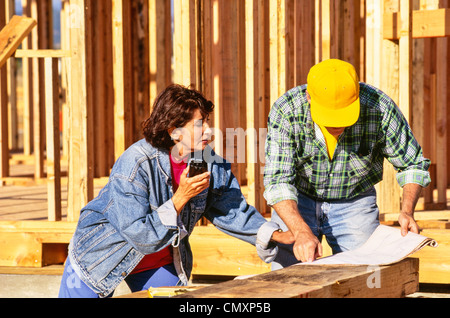 Female construction boss and male worker(, tradesman,) at site. - Stock Photo