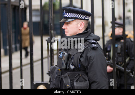 Armed police officers on patrol in Downing Street, London, England, UK - Stock Photo