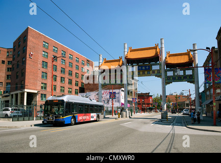 Millennium Gate and bus on East Pender Street, Chinatown, Vancouver, British Columbia - Stock Photo