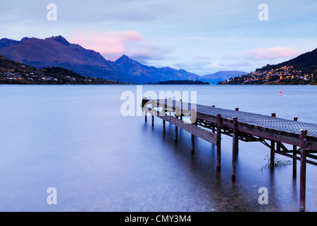 An old jetty on the shores of Lake Wakatipu, Queenstown, Otago, New Zealand, and Queenstown in the distance. - Stock Photo