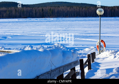 Snow covered wooden fence and lamp post with lifebuoy at snow covered frozen lake in the winter - Stock Photo
