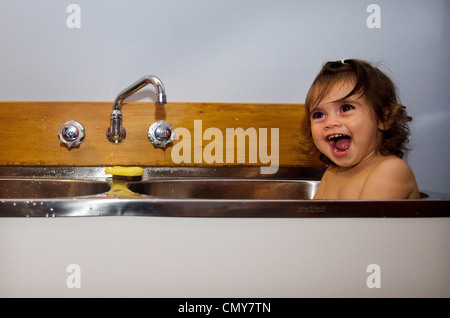 Baby having a bath in the kitchen sink - Stock Photo