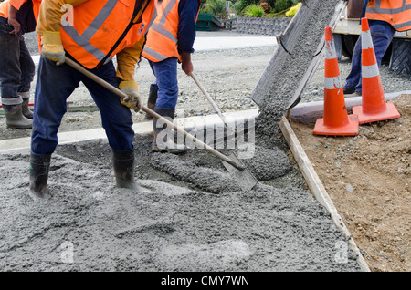 Builders pouring cement during upgrade to residential street - Stock Photo