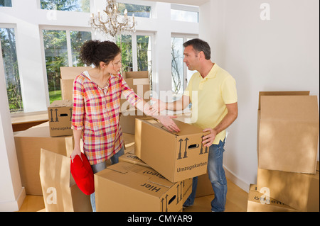 Germany, Bavaria, Grobenzell, Couple packing cardboard boxes for moving house - Stock Photo