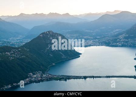 Lugano and Monte San Salvatore at Lake Lugano during sunrise, Tessin, Switzerland - Stock Photo