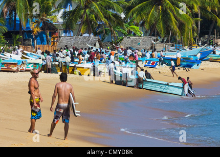 Tourists relax whilst local fishermen work on this popular surf beach; Arugam Bay, Eastern Province, Sri Lanka, - Stock Photo