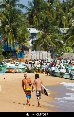Tourists stroll whilst local fishermen work on this popular surf beach; Arugam Bay, Eastern Province, Sri Lanka, - Stock Photo
