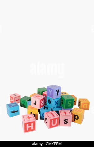 assorted childrens toy letter building blocks against a white background with copy space - Stock Photo