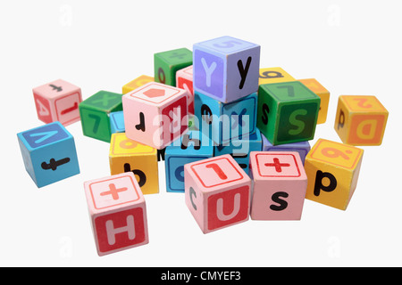 assorted childrens toy letter building blocks against a white background - Stock Photo