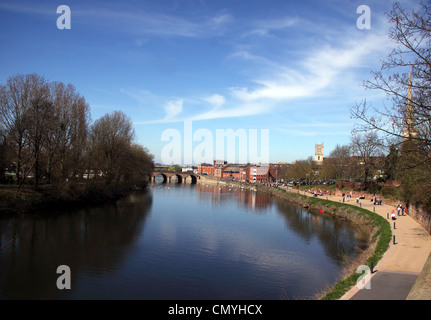 View along the River Severn at Worcester to Worcester Bridge. People walking along the footpath at the side. Blue - Stock Photo