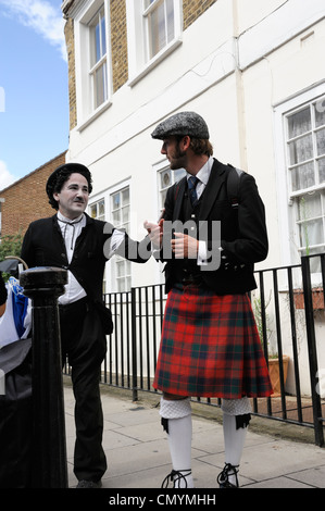 United Kingdom, London, Portobello Road market, mime street performer dressed as Charlie Chaplin ospeaking with - Stock Photo