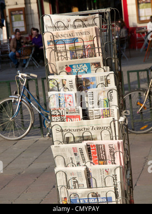 Various European newspapers in rack in front of a newsstand in Brussels, Belgium - Stock Photo