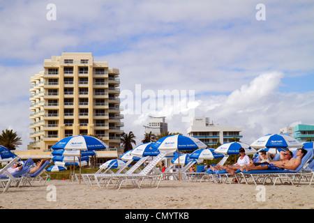 Miami Beach Florida rental lounge chairs Marriott Hotel building man woman sunbathing public beach - Stock Photo
