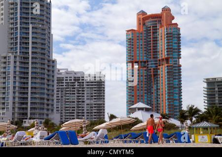 Miami Beach Florida rental lounge chairs high rise condominium building Portofino Continuum man woman public beach - Stock Photo