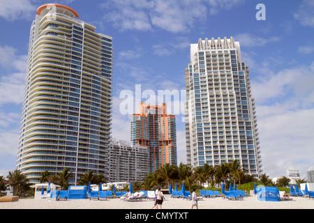 Miami Beach Florida high rise condominium building Portofino Continuum public beach rental lounge chairs - Stock Photo