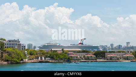 A cruise ship dominates the skyline on approach to the port in San Juan, Puerto Rico on a beautiful spring day in - Stock Photo