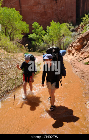 Mother and daughter backpacking in Coyote Gulch, a tributary of the Escalante River in Southern Utah. - Stock Photo