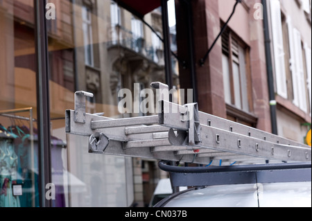 A commercial ladder on a white van. - Stock Photo