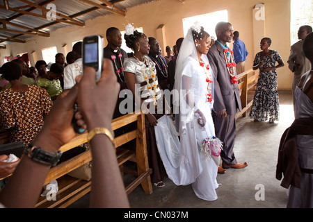 A bride and groom exit the church after their wedding ceremony in Tanzania, East Africa. - Stock Photo
