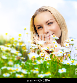 Beautiful woman enjoying daisy field and blue sky, nice female lying down in the meadow of flowers, pretty girl - Stock Photo
