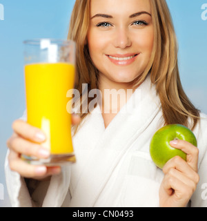 Healthy lovely young woman dieting, beautiful girl holding orange juice and green fresh apple fruit,smiling female - Stock Photo