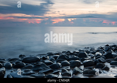 Waves lapping rocks at Pebbly Beach at dawn, near Cairns, Queensland, Australia - Stock Photo