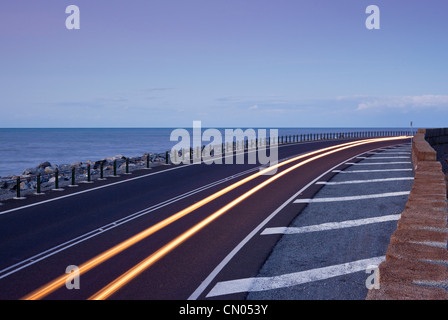 Car light trails on coastal highway.  Captain Cook Highway between Port Douglas and Cairns, Queensland, Australia