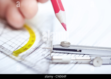 Human hand drawing engineering scheme with red pencil. Close-up photo - Stock Photo