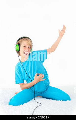 young teen kid playing air guitar and listening to music - Stock Photo