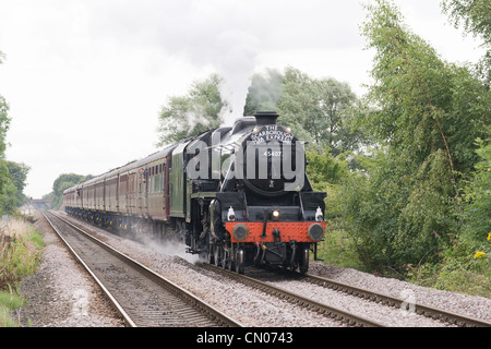 Steam locomotive pulling a passenger train on the main line - Stock Photo