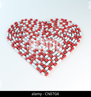 Red and white capsules forming a heart shape - cardiology concept - Stock Photo