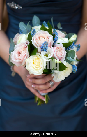 woman in a blue dress holding a bouquet of spring flowers including roses, muscari and ranunculus