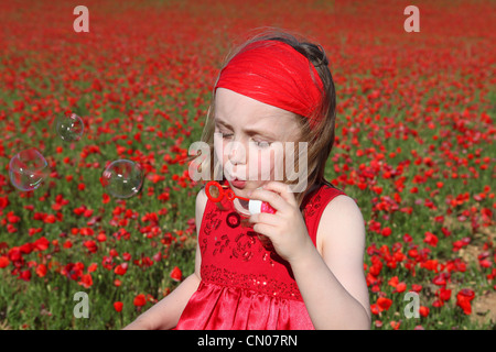 little girl blowing bubbles playing outdoors in summer - Stock Photo