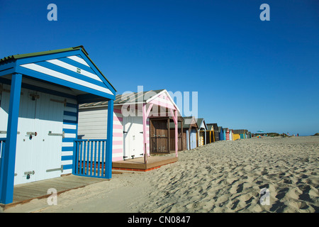 England, West Sussex, West Wittering Beach, Colourful beach huts along sandy beach. - Stock Photo
