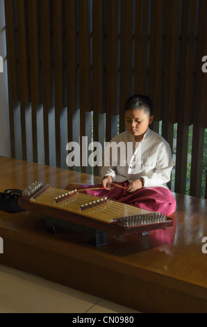 A young Thai boy plays a traditional khim instrument, Phuket, Thailand - Stock Photo