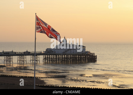 The British union jack flag flying on a flag pole with Eastbourne Pier in the background, East Sussex, England. - Stock Photo