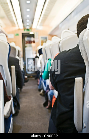 A train isle with seated passengers - Stock Photo