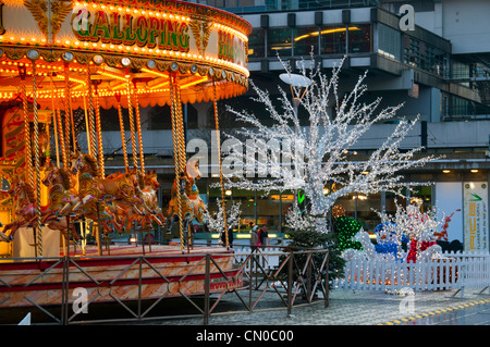 Carousel, or merry-go-round, and illuminated Christmas decorations, Piccadilly Gardens, Manchester, England, UK - Stock Photo