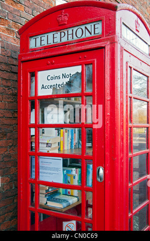 Book exchange kiosk in the village of Eaton, Nottinghamshire, England, UK.  A former telephone box converted to - Stock Photo