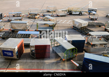 Empty luggage containers on the apron of an airport. - Stock Photo