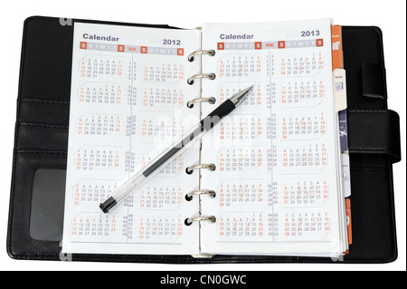 Calendar in notebook with a pen on it - Stock Photo