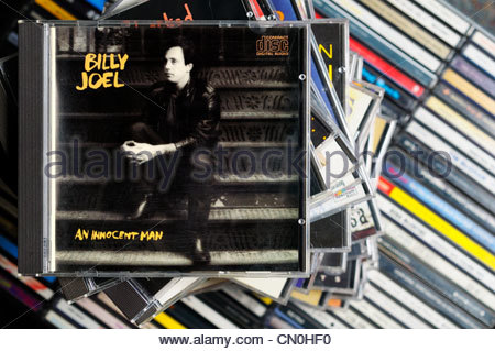 Billy Joel An Innocent Man album on a stack of CD cases, England - Stock Photo