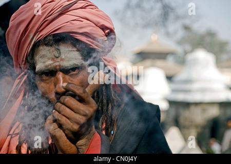 Sadhu smoking chilum (clay pipe ) during Shivaratri festival at Pashupatinath , Kathmandu , Nepal - Stock Photo