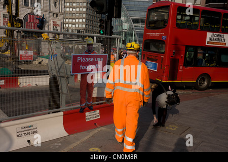 Real passing construction worker and a scaled human workman figure who warns pedestrians to stay on established - Stock Photo