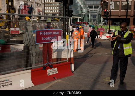 Man checks his watch near a scaled human workman figure who warns pedestrians to stay on established footpath, and - Stock Photo