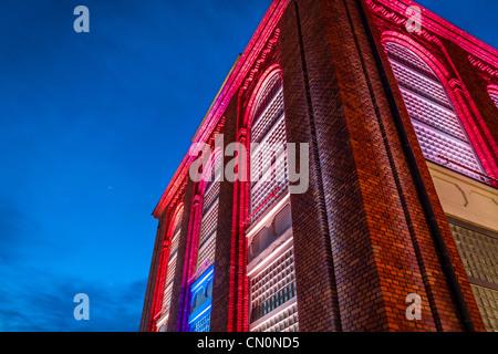 Beautifully renovated old building illuminated at night - Stock Photo