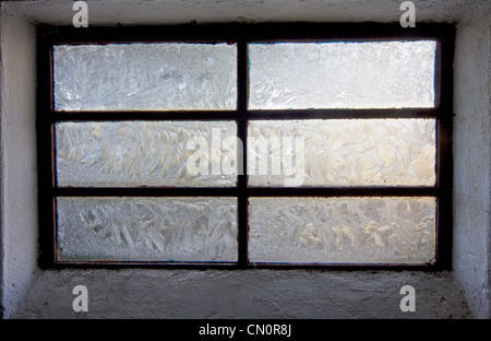 Fern-like structures in frostwork on a window of a stable - Stock Photo