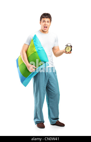 Full length portrait of a shocked male holding a pillow and alarm clock - Stock Photo