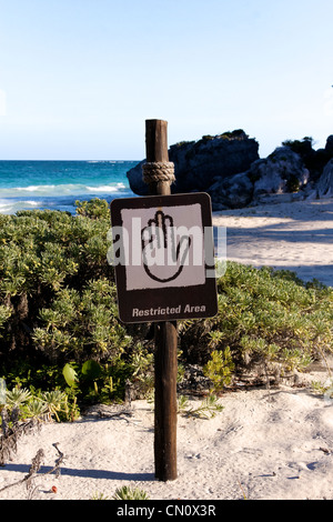 Sign denying access to a beautiful Caribbean beach (portrait format). - Stock Photo