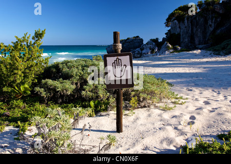 Brown and tan sign showing a hand pictogram at a beautiful Caribbean beach (landscape format) - Stock Photo